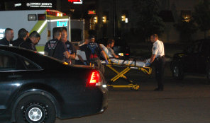 a man is transported by police and paramedics to the hospital - Photo by Shane Anthony AuroraNews1.com
