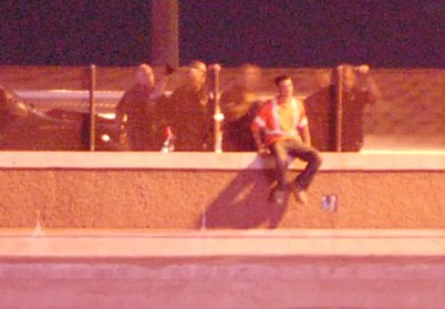 Man poised to jump or fall off of I-225 bridge