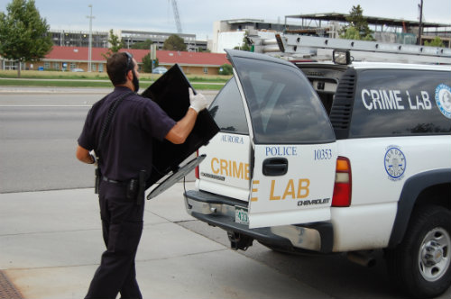 An Aurora CSI investigator loads a TV believed to be stolen into his car - Photo by Shane Anthony AuroraNews1.com