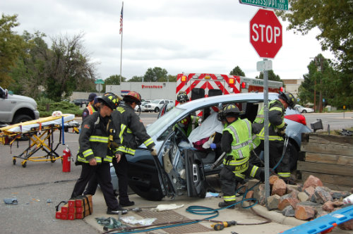 The female driver of this car is covered with a sheet to protect her during the extrication process - Photo by Shane Anthony AuroraNews1.com