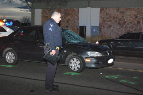 An Aurora Police Sergeant examines the accident scene.  Photo by Shane Anthony AuroraNews1.com