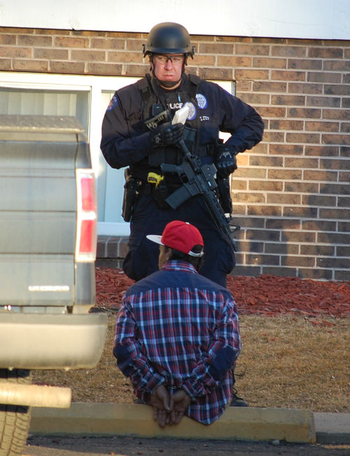 A cop stands guard over a suspect.  Exclusive Photo by Shane Anthony AuroraNews1.com