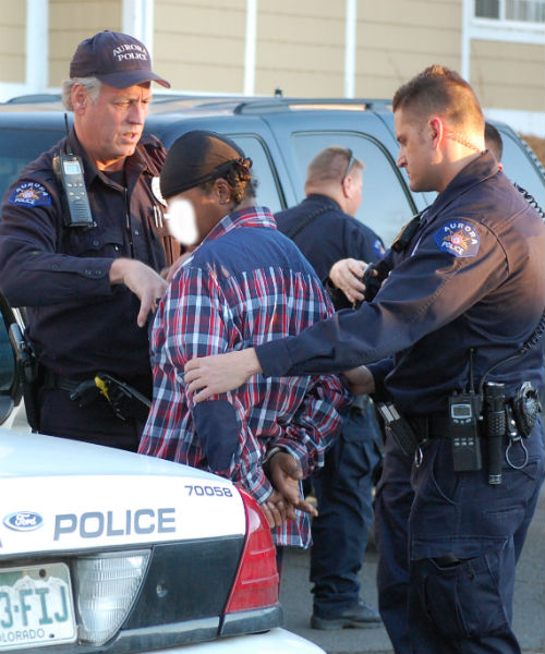 Cops escort and arrested prisoner to an awaiting patrol car.  Exclusive photo by Shane Anthony AuroraNews1.com
