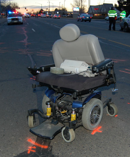 A motorized wheelchair sits in the road on S. Peoria St. where a woman was killed by a delivery truck.  Photo by Shane Anthony AuroraNews1.com