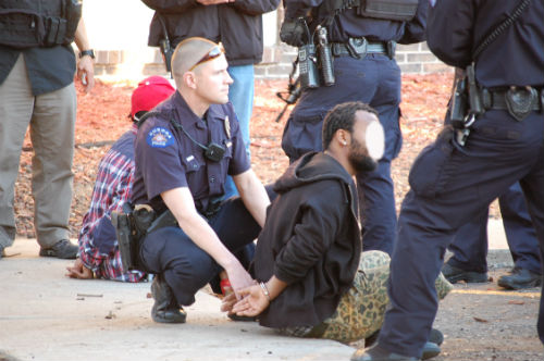 An officer kneels by 2 suspects.  Exclusive photo by Shane Anthony AuroraNews1.com