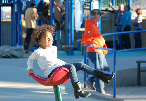 This little girl is all smiles at she twirls in the warm January sun today.  Photo by Shane Anthony AuroraNews1.com