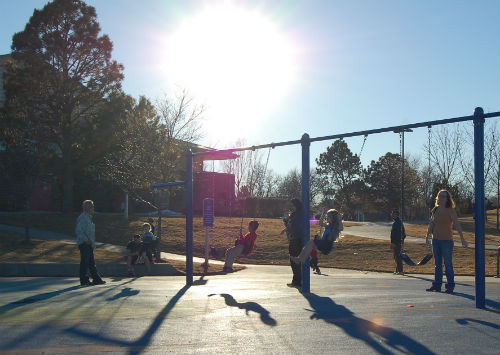 Kids swing in the January sun.  Photo by Shane Anthony AuroraNews1.com