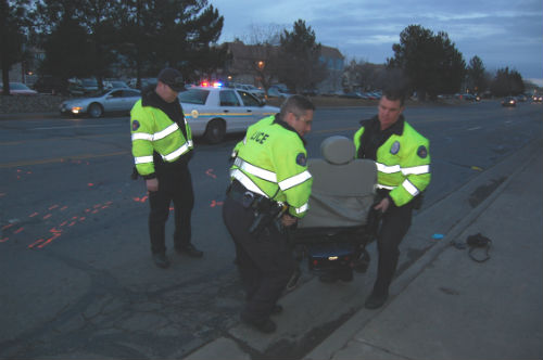APD Traffic Investigators remove a motorized wheelchair from the road after the chair rider was struck and killed by a meat delivery truck.  Photo by Shane Anthony AuroraNews1.com