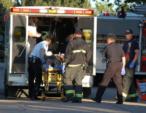 A woman who was assaulted with a rock is loaded into an ambulance.  Photo by Shane Anthony AuroraNews1.com